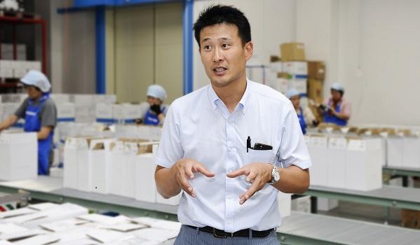 波動のある出荷件数に対応できるラインの前にて話をする大野木 俊介氏